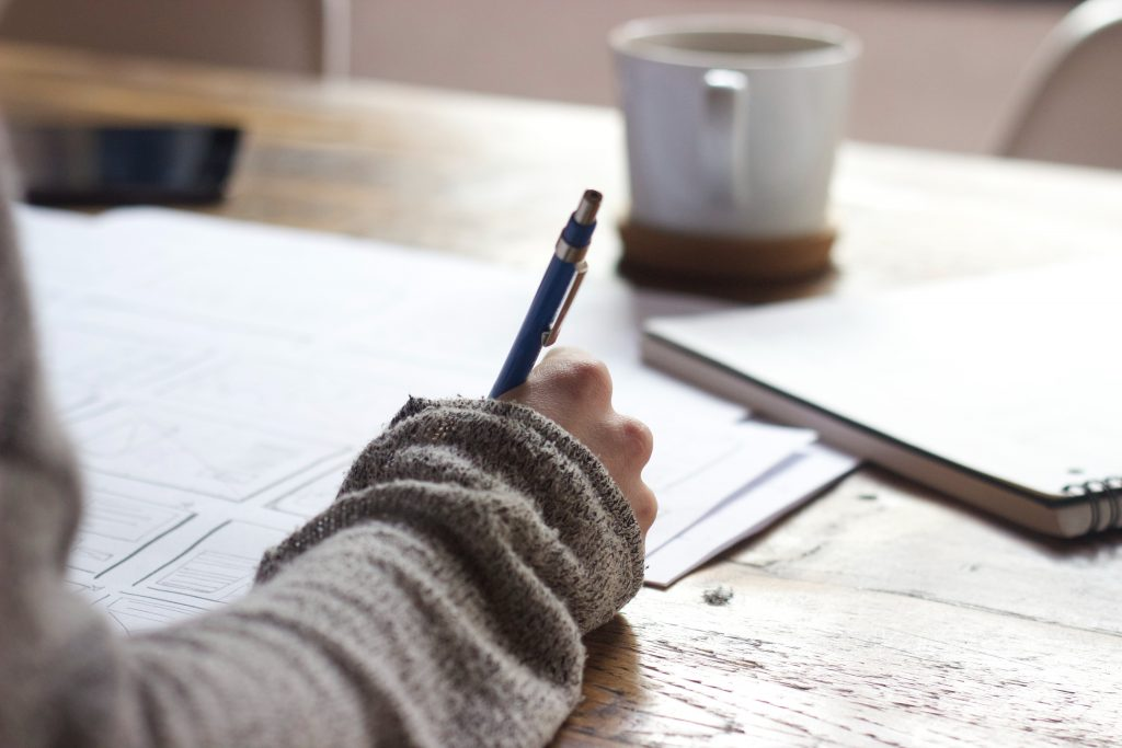 stock image of someone studying with notebooks and a cup of tea