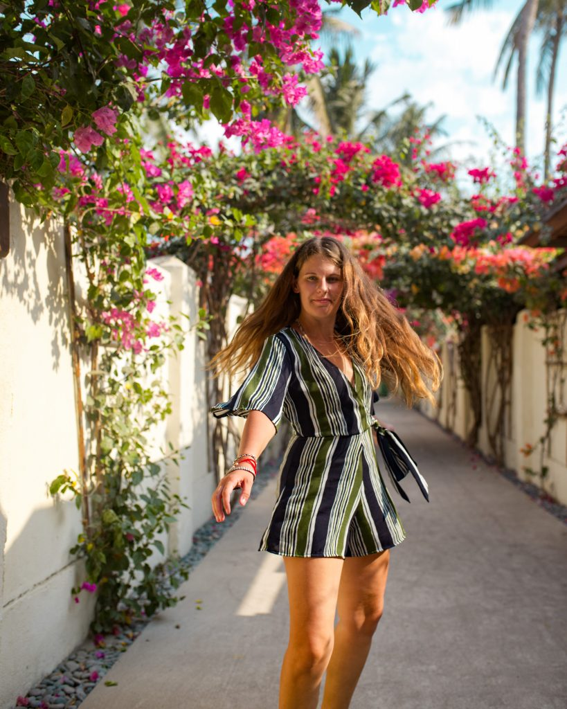Steph smiling in a striped playsuit, captured mid-twirl in a white-walled street surrounded by pink flowers