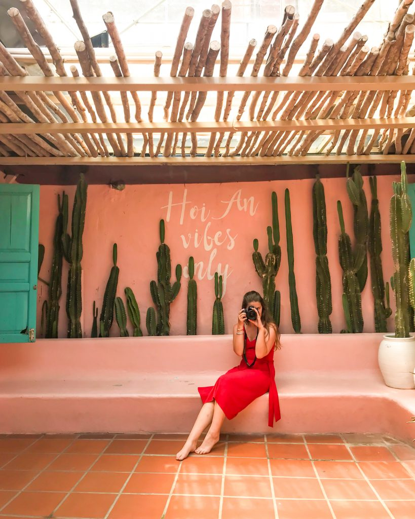 "Steph is wearing a red dress and holds a camera up to her eye. She's sat in front of a pink wall with cacti growing along it. Painted white writing on the wall says ""hoi an vibes only"""